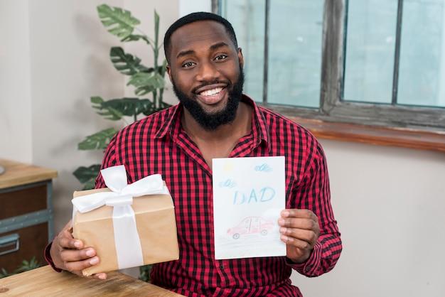 Schwarzer mann, der grußkarte und geschenk hält