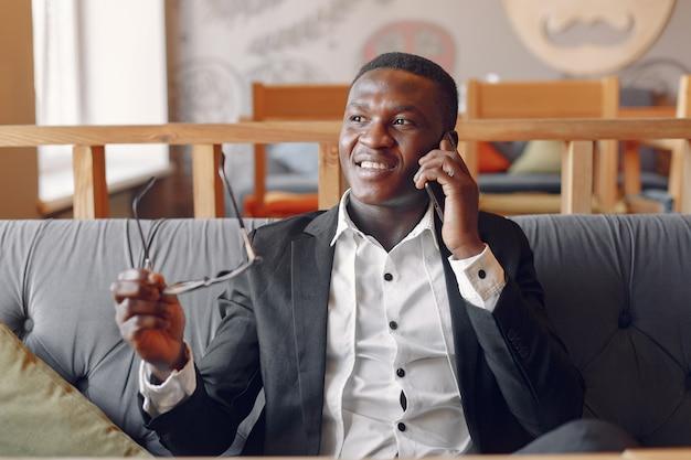 Schwarzer mann, der in einem café mit telefon sitzt