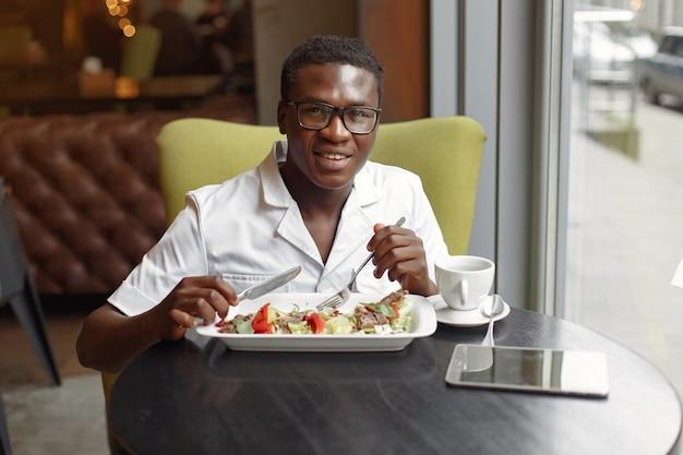 Schwarzer mann, der in einem café sitzt und einen gemüsesalat isst