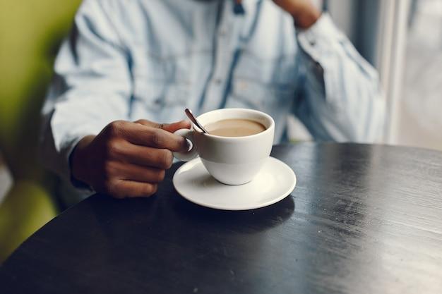 Schwarzer mann, der in einem café sitzt und einen kaffee trinkt