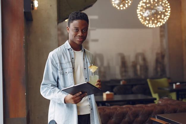 Schwarzer mann, der in einem café steht und die tablette benutzt