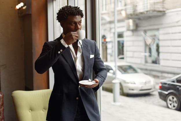 Schwarzer mann, der in einem café steht und einen kaffee trinkt