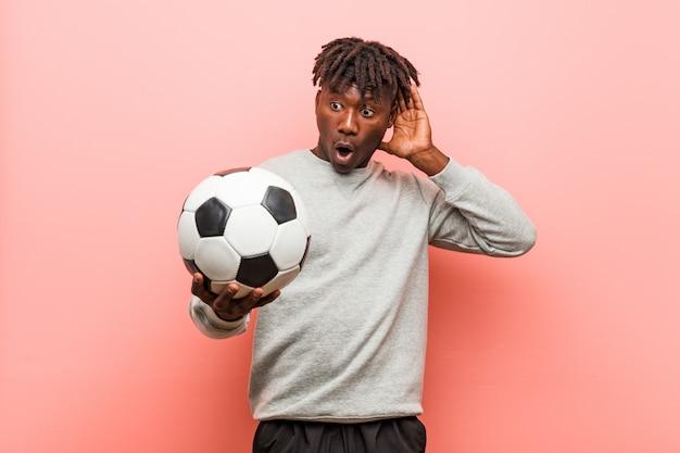 Schwarzer mann der jungen eignung, der einen fußball versucht, einen klatsch zu hören hält.