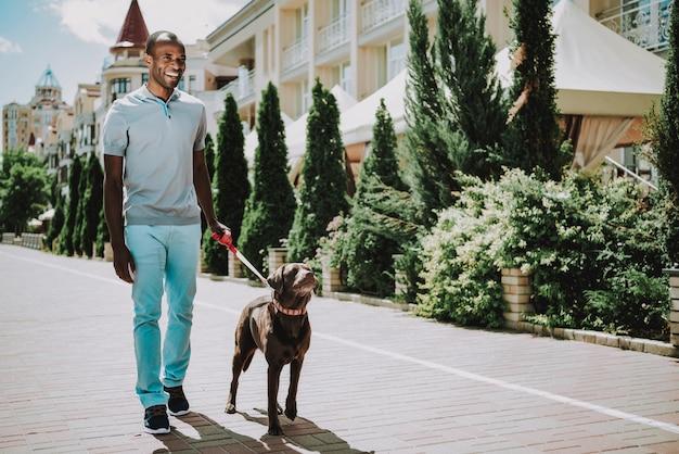 Schwarzer mann, der mit hund im park geht.