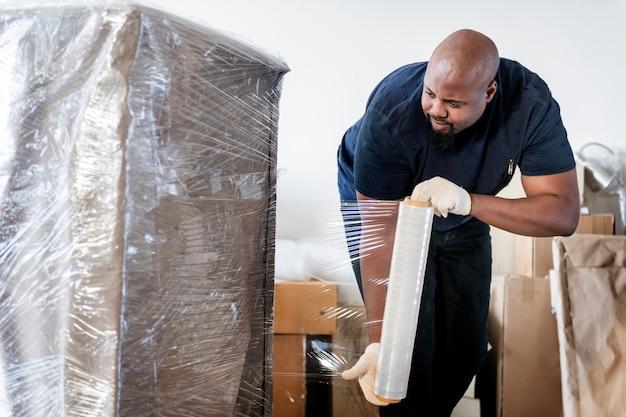 Schwarzer mann, der möbel bewegt