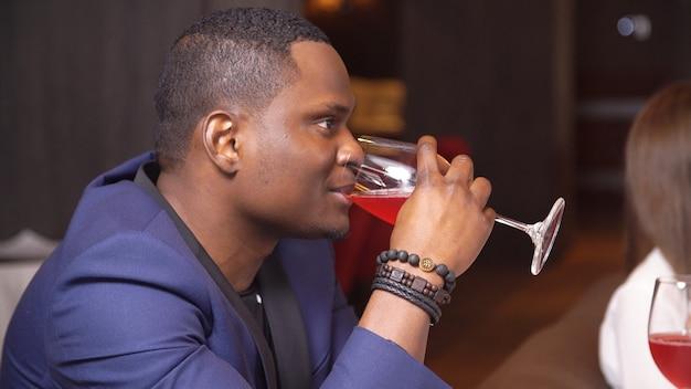 Schwarzer mann, der rotwein im restaurant trinkt.