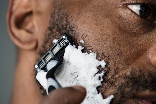 Schwarzer mann, der seinen bart rasiert