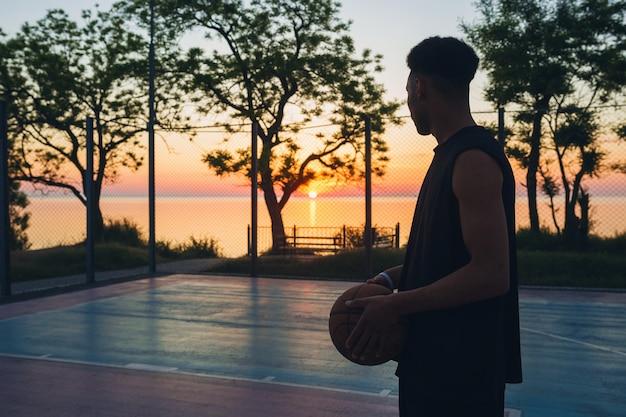 Schwarzer mann, der sport treibt, basketball auf sonnenaufgang, silhouette spielend