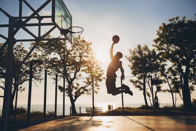 Schwarzer mann, der sport treibt, basketball auf sonnenaufgang spielt, silhouette springt