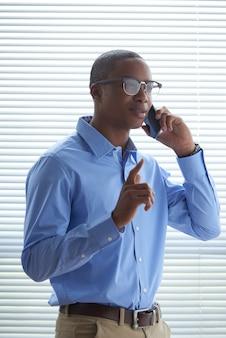 Schwarzer mann, der telefonanruf gegen das fensterladenfenster macht