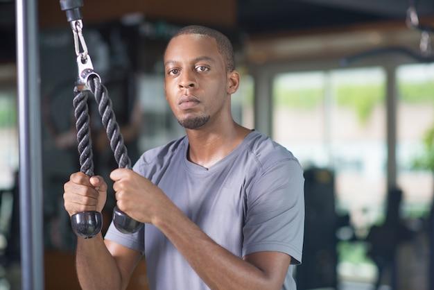 Schwarzer mann, der turnhallenausrüstung verwendet und kamera betrachtet