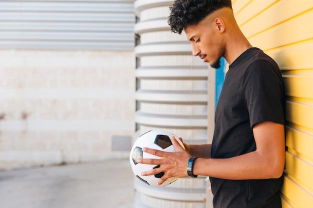 Schwarzer mann, der unten ball in den händen betrachtet