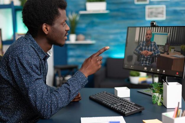 Schwarzer mann, der während der online-videoanruf-konferenz bei der marketing-präsentation mit einem ferngesteuerten behinderten-lehrer spricht. teenager mit telearbeit-telefonkonferenz mit computer