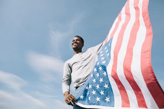 Schwarzer mann, der wellenartig bewegende amerikanische flagge hält