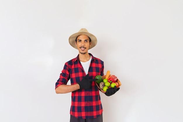 Schwarzer mann des bauern mit hut und handschuhen, die einen korb des gemüses (karotte, zitrone, tomaten, chayote und rübe halten) lokalisiert im weißen hintergrund halten