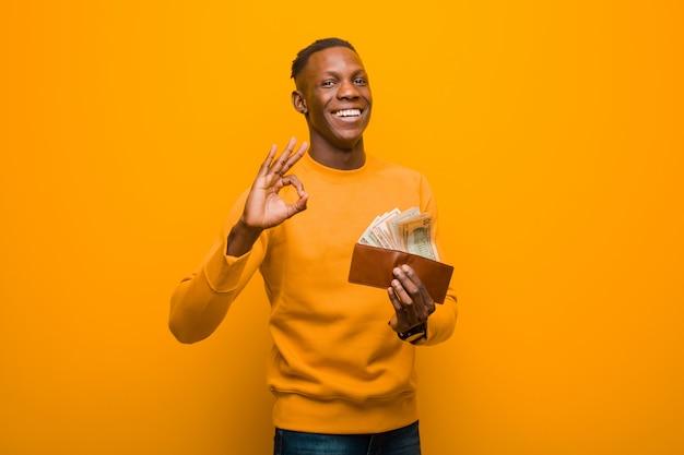 Schwarzer mann des jungen afroamerikaners gegen orange wand, geldkonzept.