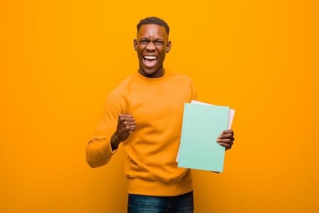 Schwarzer mann des jungen afroamerikaners gegen orange wand mit einem buch
