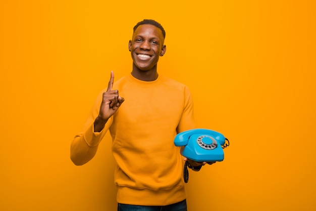 Schwarzer mann des jungen afroamerikaners gegen orange wand mit einem weinlesetelefon