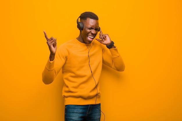 Schwarzer mann des jungen afroamerikaners gegen orange wand mit kopfhörern