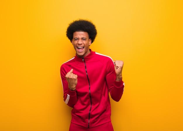Schwarzer mann des jungen sports über einer orange wand, die nicht aufgibt