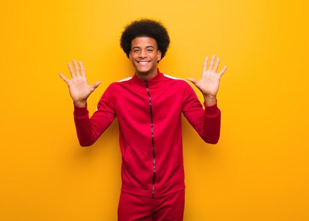 Schwarzer mann des jungen sports über einer orange wand, die nr. zehn zeigt