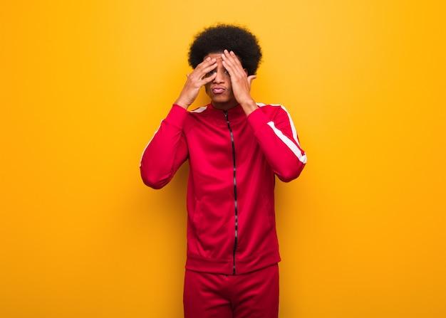 Schwarzer mann des jungen sports über einer orange wand fühlt sich besorgt und erschrocken