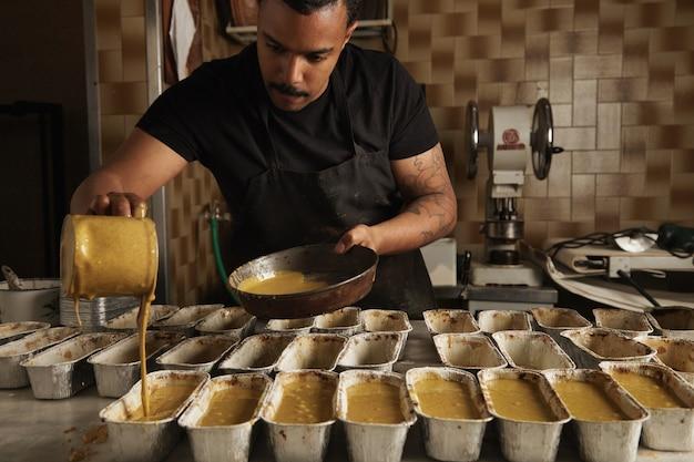 Schwarzer mann gießt leckeren flüssigen kuchenteig aus messbecher auf spezielle metallfolienformen, bevor er im ofen kocht. professioneller kochprozess in der handwerklichen bäckerei