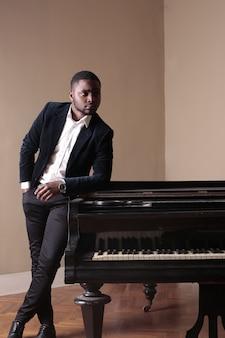 Schwarzer mann im anzug mit einem klavier