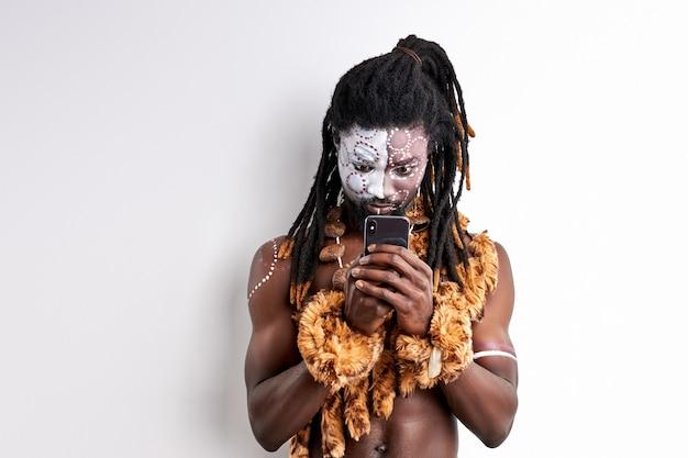 Schwarzer mann im ethnischen umhang schaut auf smartphone, versucht zu benutzen, studiert mit interesse.