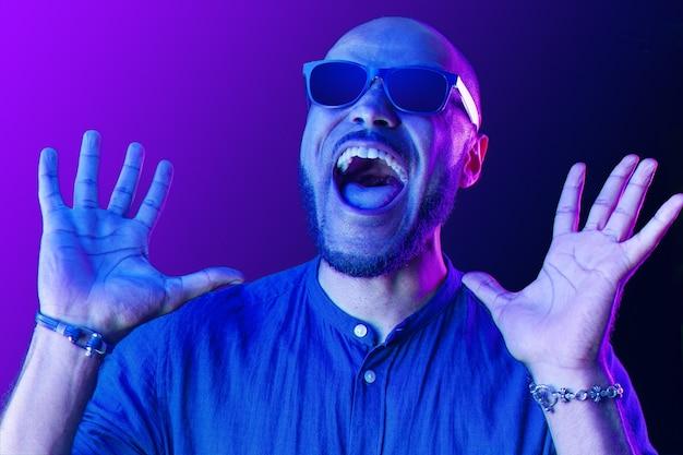 Schwarzer mann in den gläsern, die mit glück im neonlicht schreien