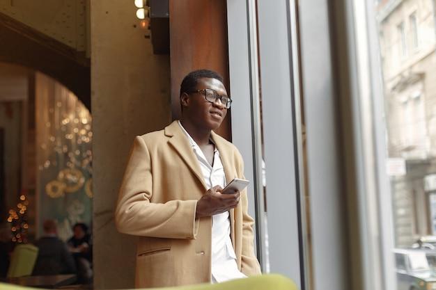 Schwarzer mann in einem braunen mantel, der mit handy steht
