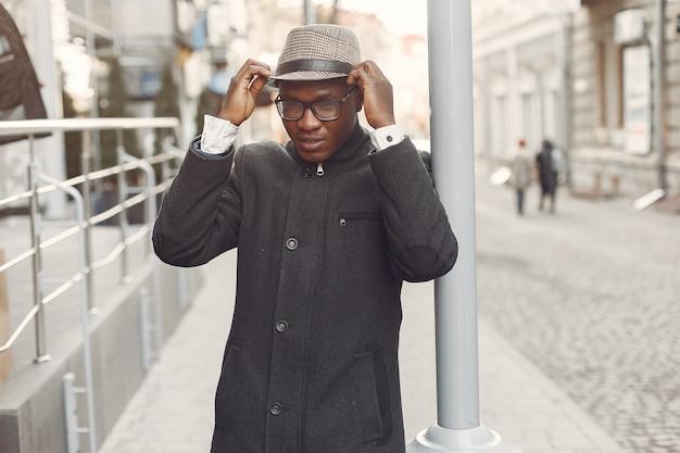 Schwarzer mann in einem schwarzen mantel in einer herbststadt