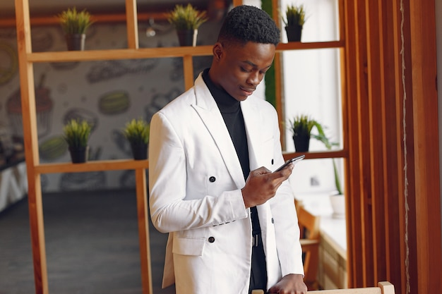 Schwarzer mann in einer weißen jacke, die mit einem telefon steht