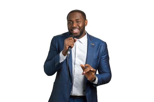 Schwarzer mann lächelt und singt. schwarzer mann im anzug mit mikrofon.