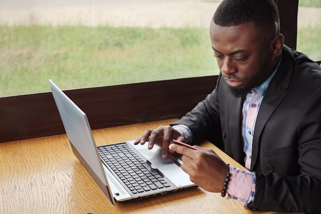 Schwarzer mann macht zahlung bankkarte auf laptop. online-shopping im café sitzen. junger afroamerikanischer geschäftsmann kauft online und gibt seine daten von der kreditkarte in den computer ein, seitenansicht. kerl kunde.