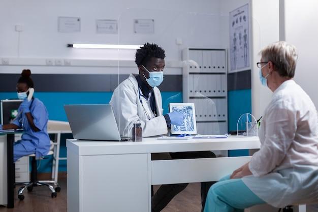 Schwarzer mann mit arztberuf, der röntgenstrahl auf moderner tablette hält
