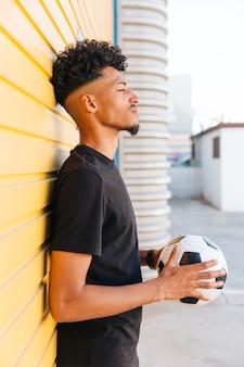 Schwarzer mann mit dem ball, der gegen wand steht