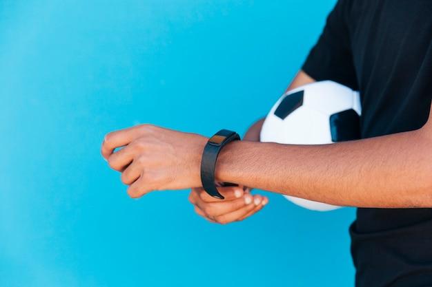 Schwarzer mann mit dem fußball, der intelligente uhr repariert