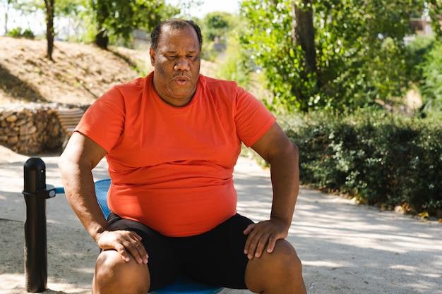 Schwarzer mann mit der korpulenz, die nachdem dem trainieren sitzt, um gewicht zu verlieren