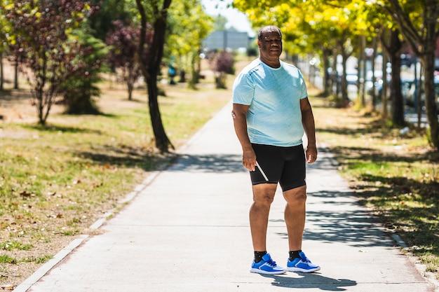 Schwarzer mann mit der krankhaften korpulenz, die übung im park tut