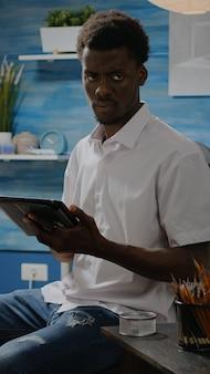 Schwarzer mann mit künstlerischen fähigkeiten mit tablet für vasendesign im werkstattstudio. person afroamerikanischer abstammung, die mit digitaler technologie zeichnung auf weißer leinwand und staffelei erstellt