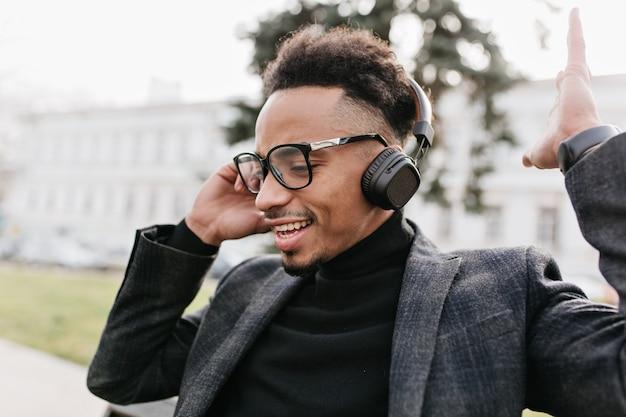 Schwarzer mann mit trendiger afrikanischer frisur, die musik auf stadt hört. hübscher mulattentyp in der freizeitjacke und in den kopfhörern, die im park aufwerfen.