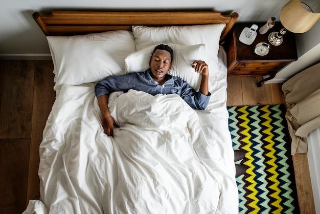 Schwarzer mann schläft auf dem bett