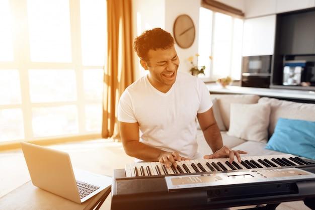 Schwarzer mann sitzt in der wohnung und spielt synthesizer.