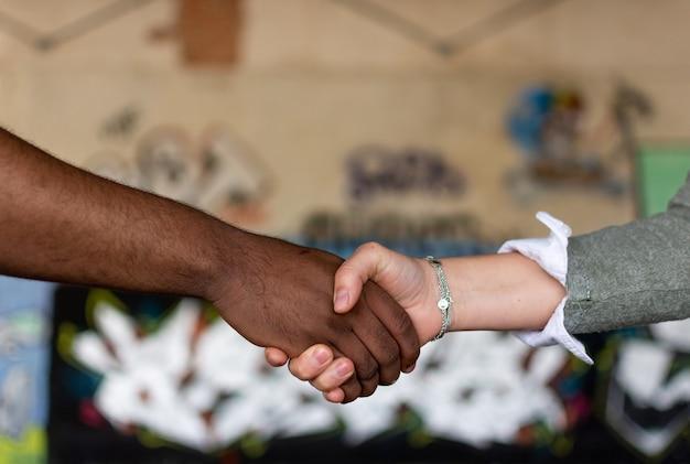 Schwarzer mann und weiße frau, die hände halten. gewerkschaftskonzept. stoppt rassismus.