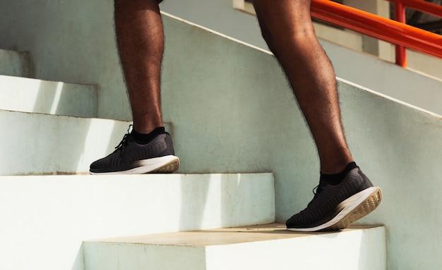 Schwarzer mannschritt des sportläufers, der zum treppensteigen hochläuft