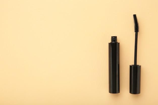 Schwarzer mascara-zauberstab und -röhre auf beigem hintergrund mit kopierraum. ansicht von oben