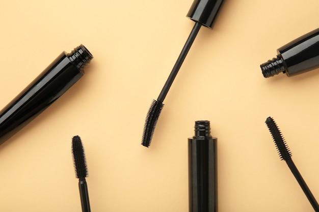 Schwarzer mascara-zauberstab und -tube auf beigem hintergrund. ansicht von oben