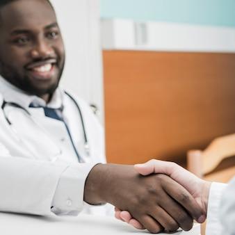Schwarzer mediziner, der hand rüttelt