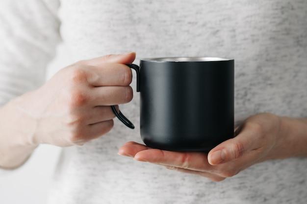 Schwarzer metallbecher für tee und kaffee in der frauenhand